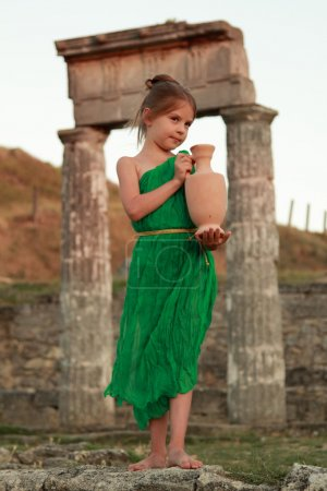 Beautiful young Greek goddess in emerald green vintage dress holding of an ancient amphora.