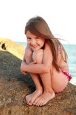 Cute little girl in a bathing suit sitting on a large rock by the sea.
