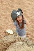Krásná holčička v pirát kostým s rozpustilým úsměvem drží mapa