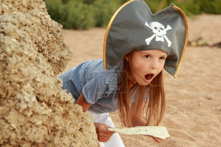 Beautiful little girl in a pirate costume with a wicked grin is holding a map
