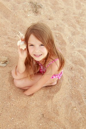 European smiling little girl in a pink swimsuit sitting on a background of sea sand