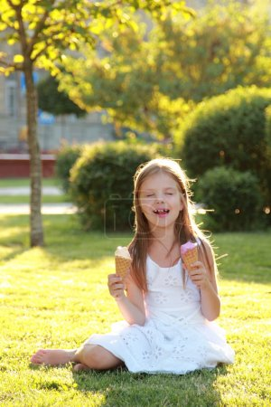 Contented smiling little girl is holding two ice creams sitting on the grass