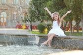 Radostné mladá dívka s nádhernými vlasy namočí nohy v fontána v horkém letním dni