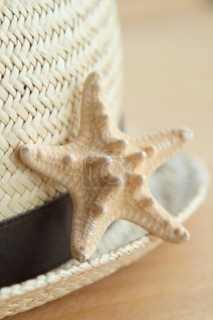 Starfish and summer hat on the old wooden background
