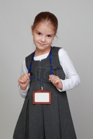 Girl in a school uniform with a badge