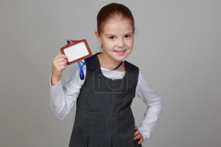 Photo for Image of lovely little girl in a school uniform with a name tag on a gray background - Royalty Free Image