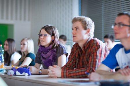 Foto de Joven, bonita estudiante universitaria sentada en un aula llena de estudiantes durante la clase - Imagen libre de derechos