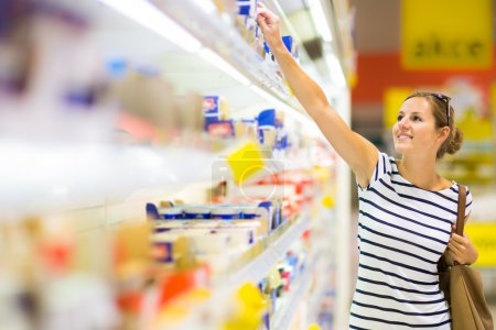 Photo for Beautiful young woman shopping for diary products at a grocery supermarket - Royalty Free Image