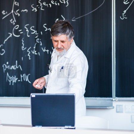 Senior chemistry professor writing on the board