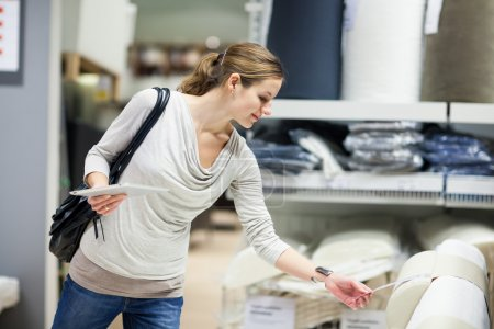 Photo for Young woman shopping for furniture in a furniture store, using her tablet computer to compare prices for dimensions - Royalty Free Image
