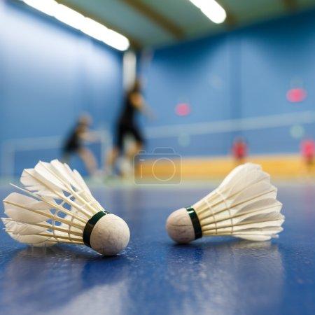 Photo pour Badminton - terrains de badminton avec des joueurs en compétition, des navettes au premier plan (DOF peu profond, image couleur tonique ) - image libre de droit