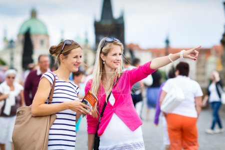 Two female tourists walking along the Charles Bridge while sightseeing in Prague