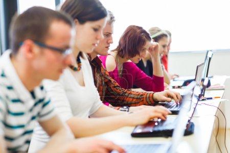 Estudiantes universitarios sentados en un aula, usando computadoras portátiles