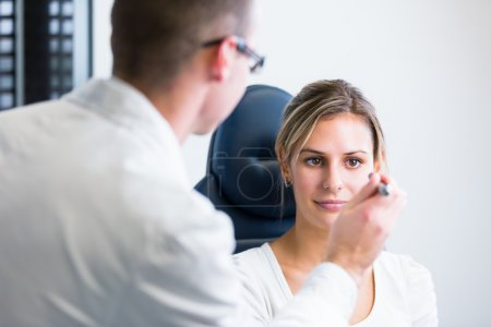 Photo for Optometry concept - pretty young woman having her eyes examined by an eye doctor (shallow DOF color toned image) - Royalty Free Image