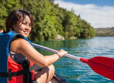 Pretty, young woman on a canoe on a lake, paddling, enjoying a l