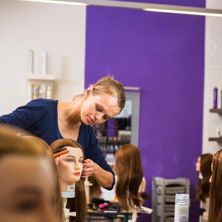 Photo pour Jolie coiffeuse - apprenti coiffeur formation sur une tête d'apprenti - image libre de droit