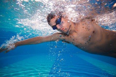 Photo pour Jeune homme nageant devant ramper dans une piscine - prise de vue sous-marine (image couleur tonique ) - image libre de droit