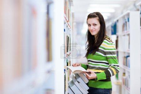 Photo pour Dans la bibliothèque - jolie, étudiante à la recherche de livres dans un lycée, bibliothèque universitaire (image couleur tonique ) - image libre de droit