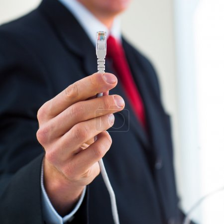 Businessman holding an ethernet cable