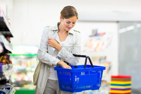Photo for Beautiful young woman shopping in a grocery store,supermarket (color toned image) - Royalty Free Image