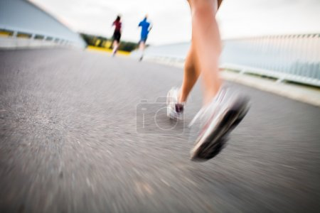 Photo for Young woman jogging outdoors (motion blurred image) - Royalty Free Image
