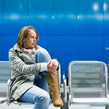 Photo for Sad and alone in a big city - Depressed young woman sitting in a metro station, feeling sorrow, regret - Royalty Free Image