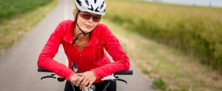 Photo for Pretty, young female biker outdoors on her mountain bike (shallow DOF, selective focus) - Royalty Free Image