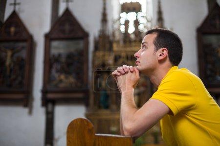 Photo pour Beau jeune homme priant dans une église - image libre de droit
