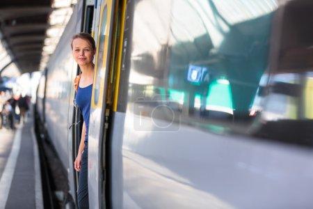 Photo pour Jolie, jeune femme dans une gare, attendant son train, embarquant dans un train (image couleur tonique ) - image libre de droit
