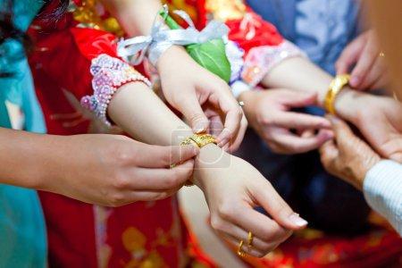 Elderly relatives presenting the golden bracelet as a blessing i