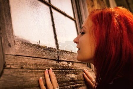 woman curiously looks in window of old house