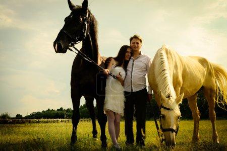 Photo pour Mariage de couple insolite heureux près de chevaux noirs et blancs - image libre de droit