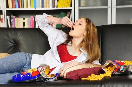 Photo for A young woman, teenager with long blond hair lolls on a black leather sofa, watching television and eating crisps and coke here. - Royalty Free Image