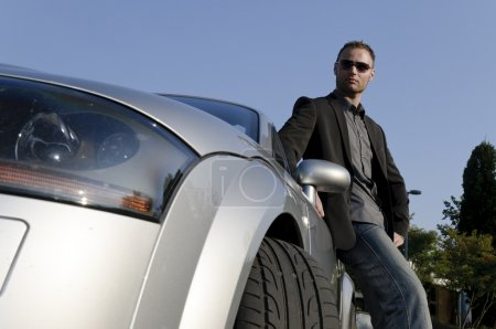 Successful businessman in front of his convertible