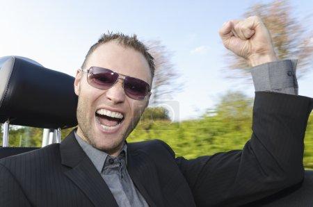 Photo pour Jeune homme en costume monté dans sa voiture de sport ouverte sur la route et rit avec enthousiasme à la caméra . - image libre de droit