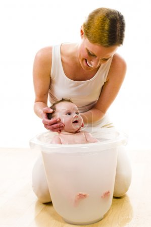 Mom bathing cute baby girl
