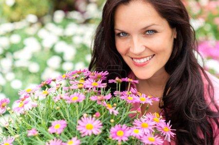 Photo pour Portrait de belle femme avec des fleurs violettes dans le magasin de jardin - image libre de droit