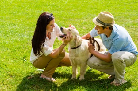 Young happy couple playing with Labrador dog
