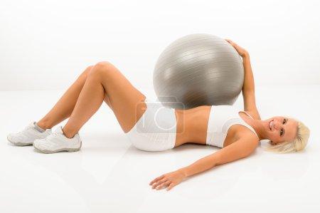 Photo pour Fitness femme blonde faisant de l'exercice avec balle de gym couché plancher blanc - image libre de droit