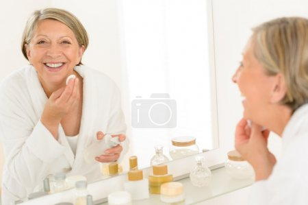 Senior woman smiling bathroom mirror reflection