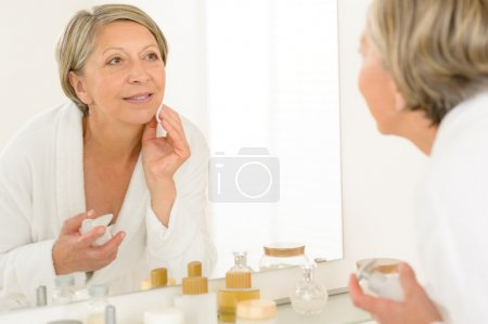 Senior woman look at herself bathroom mirror reflection