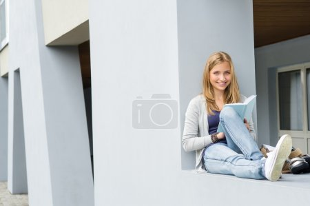 Teenage woman reading book outside of school