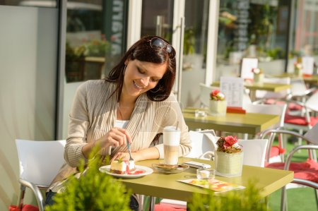 Woman at cafe eating cheesecake dessert happy