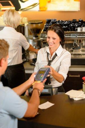 Man paying bill at cafe using card