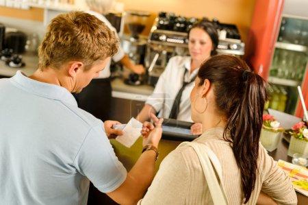 Photo pour Homme vérifiant reçu au café restaurant paiement serveuse couple bar - image libre de droit