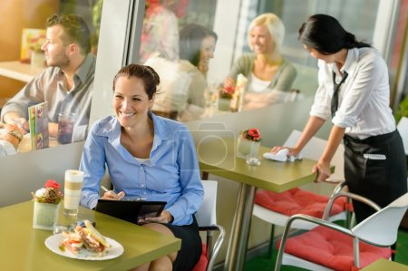 Photo for Businesswoman working in lunch break in cafe writing happy inspiration - Royalty Free Image