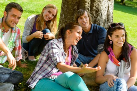 Photo for Students relaxing in schoolyard teens meadow park laughing campus young - Royalty Free Image