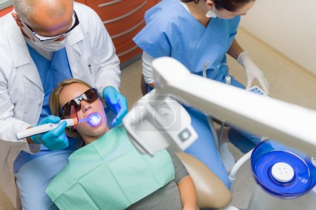 Dentist use UV lamp female patient
