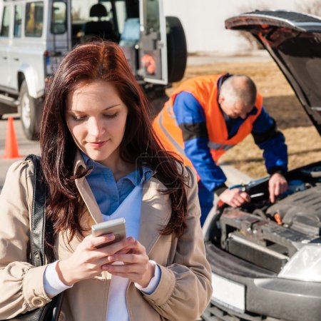Woman dialing on cellphone after car breakdown