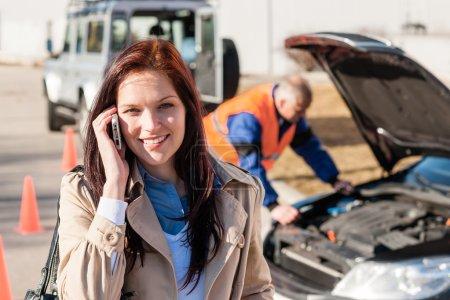 Woman talking on cellphone after car breakdown